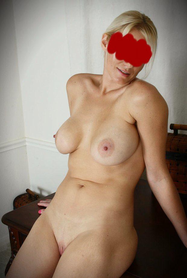 Plan cul avec une cougar blonde et sexy toute nue qui exhibe ses gros seins